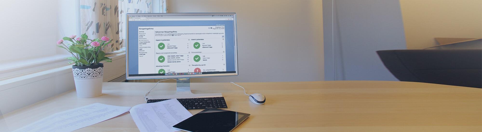 Computerskærm med tablet og papirer på skrivebord med CleanManager